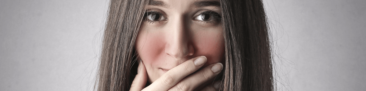 Woman with excessive facial blushing covering her mouth and smiling