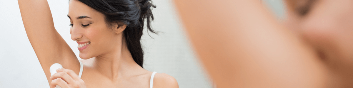 Woman wiping antiperspirant under her arms to treat excessive underarm sweating