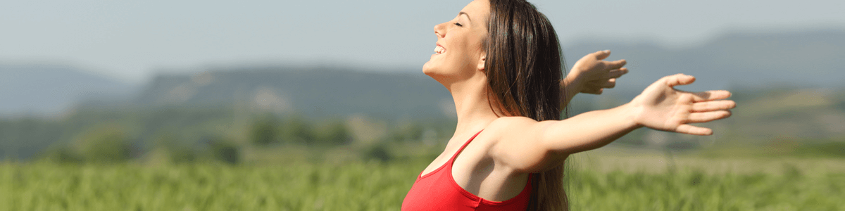 Smiling woman holding her hands out and showing her armpits thanks to Botox treatments