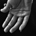Black and white picture of a hand dripping with sweat